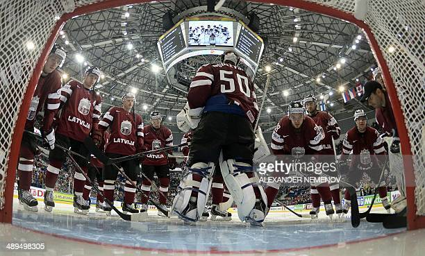 Latvia's team gather aroud their goalie Kristers Gudlevskis during a preliminary round group B game Germany vs Lavia of the IIHF International Ice...