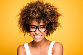 Young beautiful african american girl with an afro hairstyle. Laughing girl wearing eyeglasses. Portrait. Yellow background. Girl looking at camera.