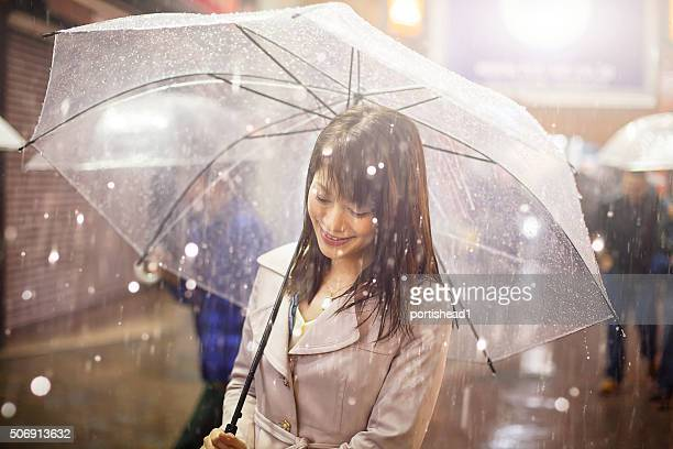 Lachen asiatische Frau mit Regenschirm