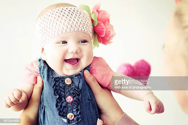 Laughing baby girl in mother's hands