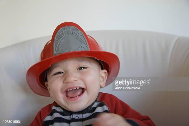 Laughing baby in fireman helmet