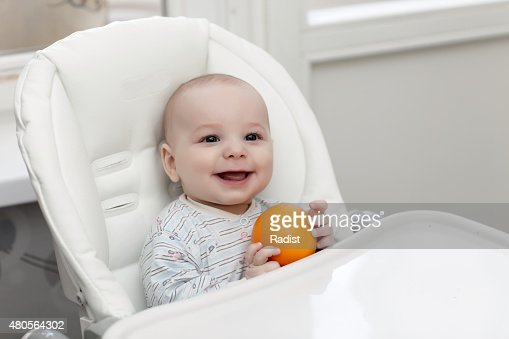Laughing baby with orange : Stock Photo