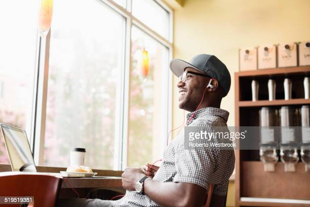 Laughing Black man using laptop in coffee shop
