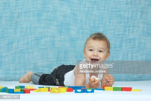Laughing boy and wooden cubes : Stock Photo