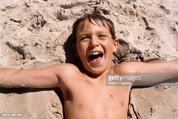 Laughing Boy Lying on Sand