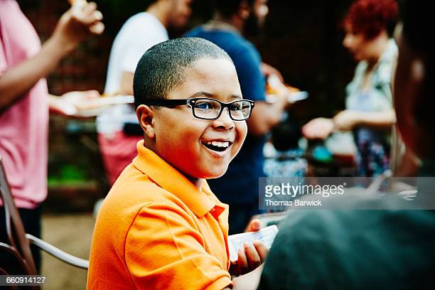 Laughing boy playing cards with family and friends
