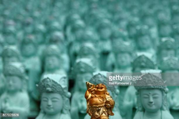 Laughing Buddha golden statue in front of many green statues