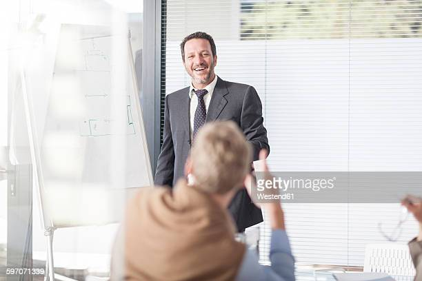 Laughing businessman at flip chart talking to colleagues