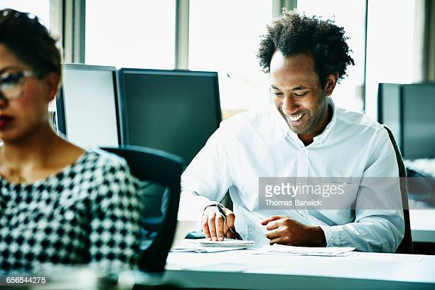 Laughing businessman working at workstation