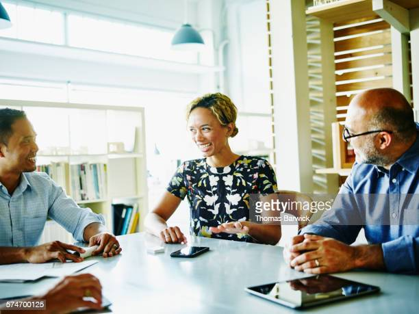 Laughing businesswoman leading team meeting