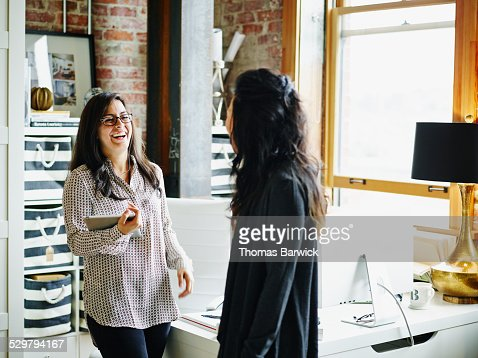Laughing businesswomen in discussion in office