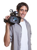 Laughing hispanic cameraman on an isolated white background for cut out