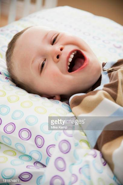 Laughing Caucasian boy laying in bed