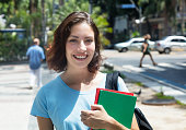 Laughing caucasian female student in the city in the summer