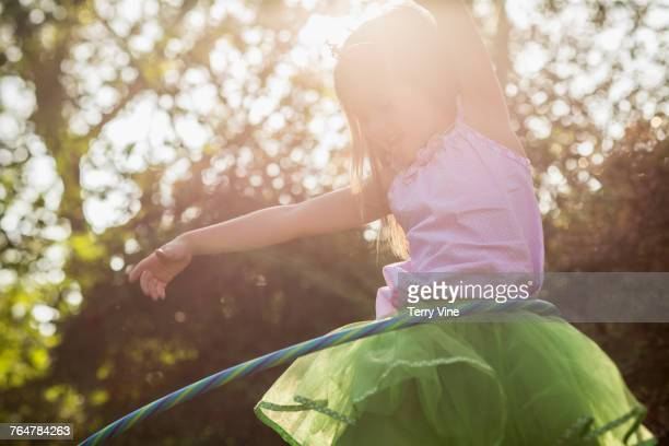 Laughing Caucasian girl spinning plastic hoop
