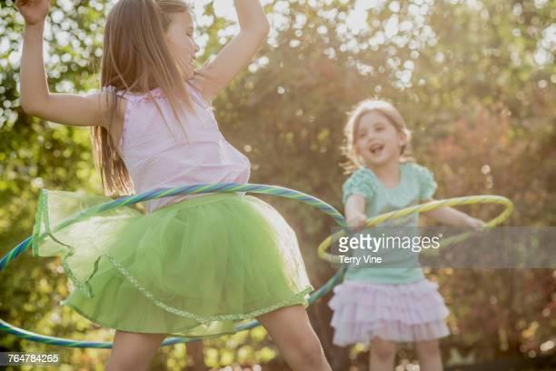 Laughing Caucasian girls spinning plastic hoop