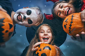 Happy brother and two sisters at Halloween. Funny kids in carnival costumes outdoors. Cheerful children and pumpkins buckets on night sky background.