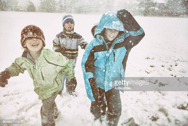 Laughing children playing in snow storm on a school field