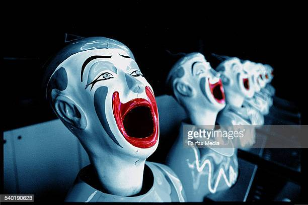 Laughing clowns in sideshow alley in a blue duotone with red mouths
