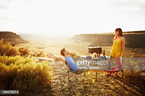 Laughing couple barbecuing at desert overlook