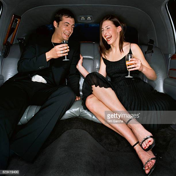 Laughing Couple Drinking Champagne in Back Seat of Limousine
