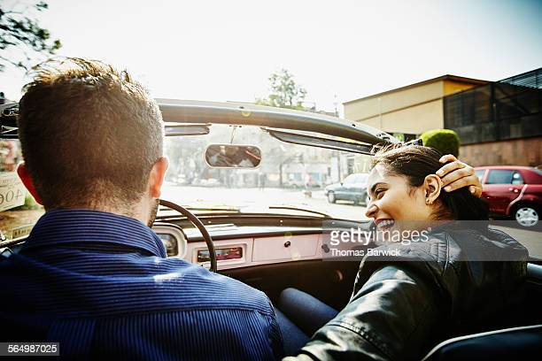 Laughing couple driving convertible at sunrise