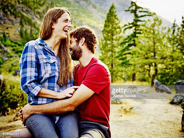 Laughing couple embracing at mountain lookout