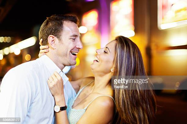 Laughing couple embracing in nighttime street