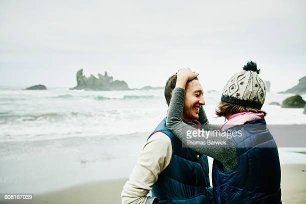 Laughing couple embracing on beach