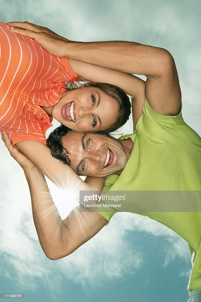 Laughing couple embracing under blue sky