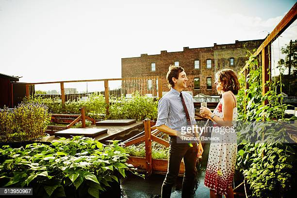 Laughing couple having drinks in rooftop garden
