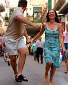 Laughing couple holding hands and running on street