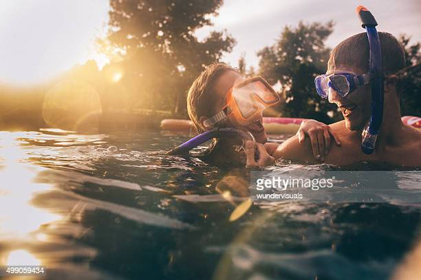 Laughing couple in pool wearing snorkelling gear with lens flare