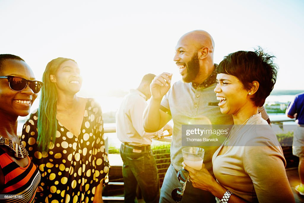 Laughing couple sharing drinks with friends