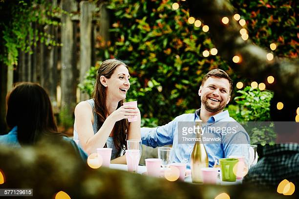Laughing couple sitting together having drinks