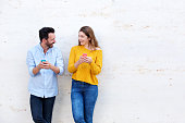 Portrait of laughing couple standing by white wall holding mobile phones