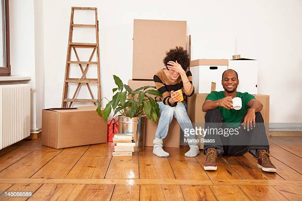 A laughing couple taking a coffee break while moving house