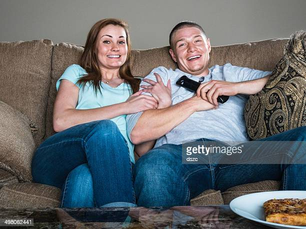 Laughing couple watches comedy TV sitting on sofa with pizza