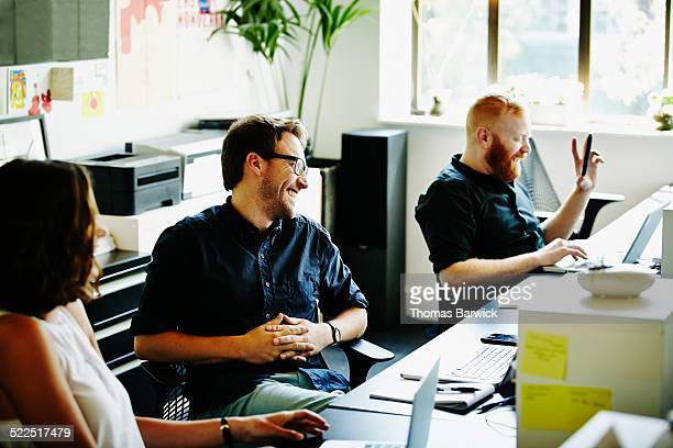 Laughing coworkers in office in discussion