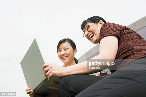 Laughing co-workers with laptop