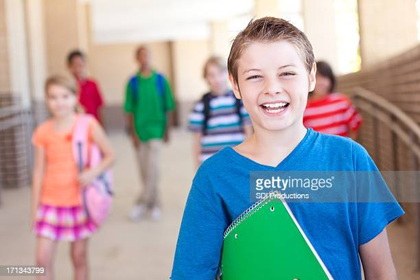 Laughing elementary school student in front of his peers