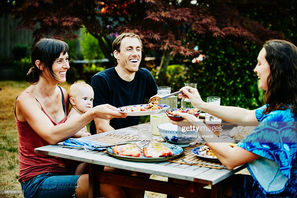 Laughing families sharing dinner in backyard : Stock Photo
