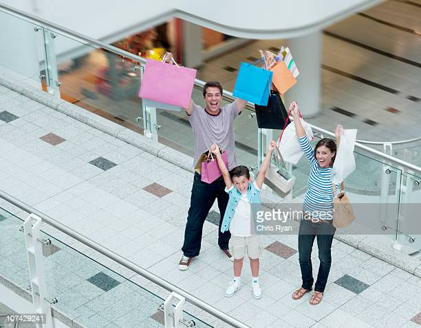 Laughing family lifting shopping bags in mall