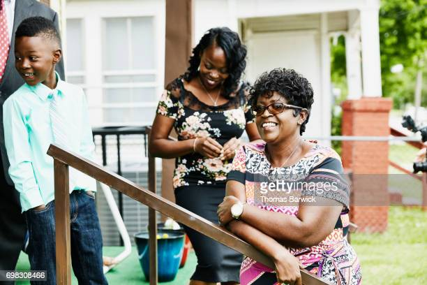 Laughing family members hanging out on front porch of home