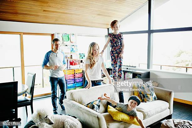 Laughing family playing together in living room