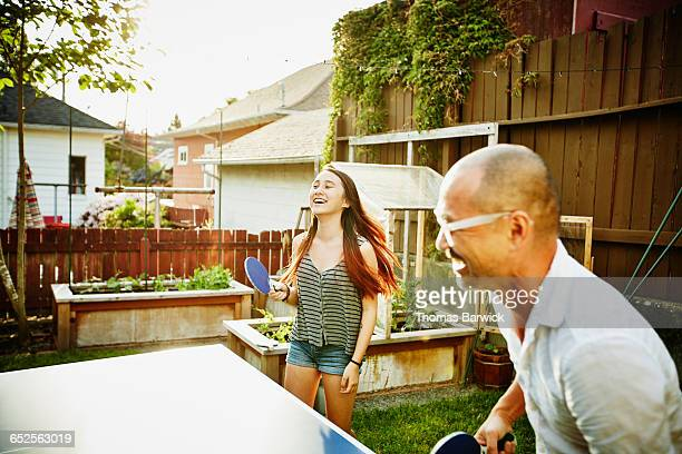 Laughing father and daughter playing ping pong