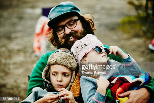 Laughing father holding son and daughter