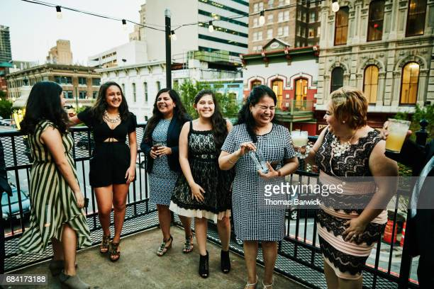 Laughing female family members on restaurant deck before dinner