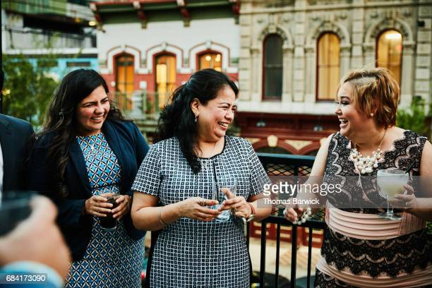 Laughing female friends sharing drinks on restaurant deck before dinner