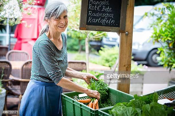 Lachen weiblichen Markt Händler am Marktstand mit Bio-Speisen